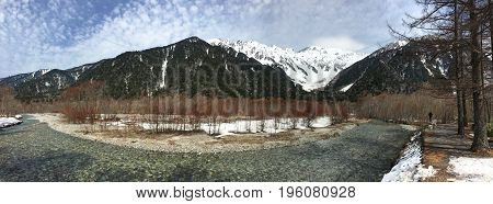 Unfrozen Azuza River in the Kamikochi National Park on background of the Mountains