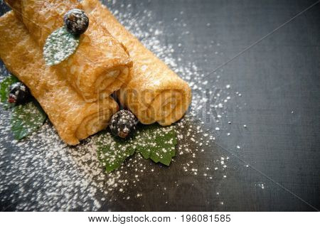 pancakes on a black background with currants and powdered sugar