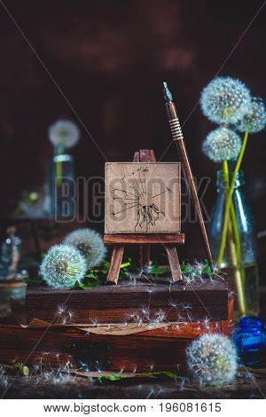 Summer still life with blowballs, a little dandelion painting on an easel, ink pen and, stack of wooden boxes on a dark wooden background