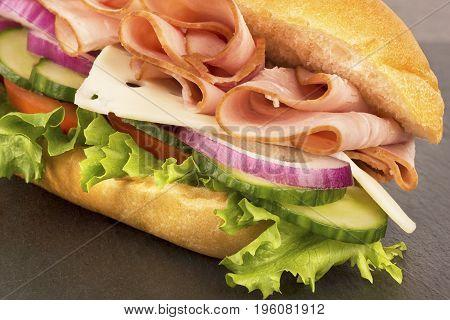 Close up on submarine ham sandwich disposed on grey slate.