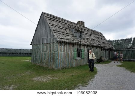 MACKINAW CITY, MICHIGAN / UNITED STATES - JUNE 18, 2017: Visitors enjoy exploring buildings in Fort Michilimackinac, in the Colonial Michilimackinac State Park.
