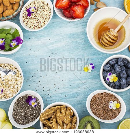 Ingredients for a healthy breakfast, nuts, oatmeal, honey, berries, fruits, blueberry, orange, Edible flowers, Chia seeds, flax seeds, goji berries, almonds walnuts The concept of natural organic food Top view