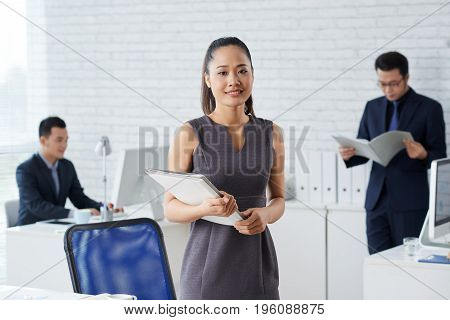 Portrait of young Vietnamese business lady with folders