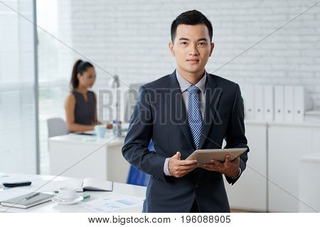 Portrait of young Asian businessman with tablet computer