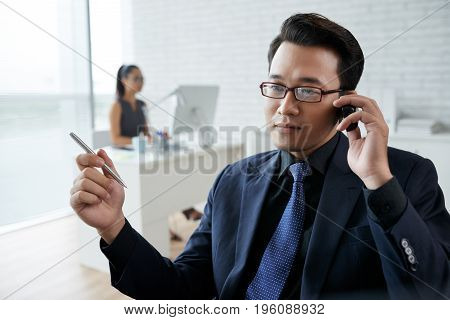 Portrait of Asian entrepreneur calling on the phone