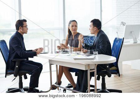 Young Asian business people having brainstorming session