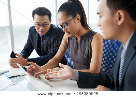 Business team discussing information on tablet computer