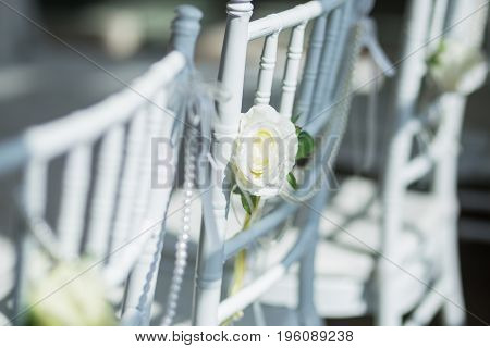 white chairs with flowers decoration for a wedding ceremony.