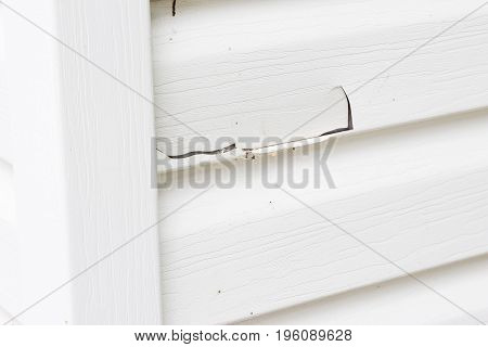 close up horizontal  close up image of white plastic siding with a big crack in it.