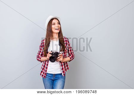 Young Cheerful Brunette Female Tourist Photographer Is Smiling On The Light Blue Background. She Is