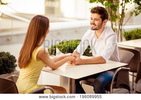 Happy Together. Two Young Cute Lovers Are Sitting In Light Cafe On A Sunny Day And Hold Each Other`s