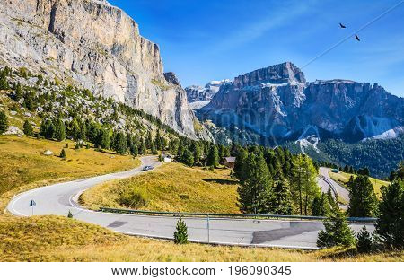 Picturesque road through the Sella Pass, Dolomites. The concept of ecological and extreme tourism. Impressive ridge of dolomite rocks.