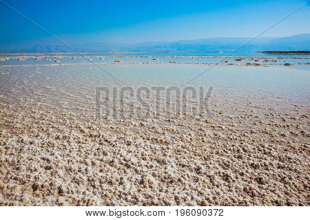 Hot summer day at the famous seaside resort. The shallow sea is covered with evaporated salt. The Dead Sea, Israel. The concept of medical and ecological tourism
