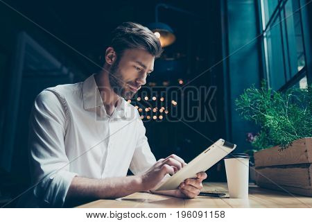 Side View Of A Young Sexy Entrepreneur, Browsing On His Tablet In A Dark Designed Modern Cafe, Well