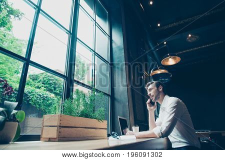 Low Angle View Of A Successful Young Man, Having A Business Conversation,  At Work Station In A Mode