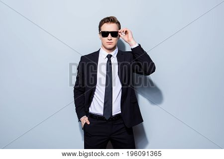 Harsh Agent, Standing On A Pure Background. He Looks Stunning And Severe, Wearing Suit And Sunglasse