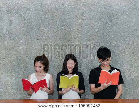 Young Syudents Group SmileReading School Folders Book on Table and Gray Background in Education Campus University