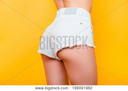 Back View Of Sexy Girl Showing Her Butt In Tight White Jeans Shorts On Bright Yellow Background. So
