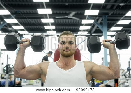 Athlete Doing Exercise For Shoulders With Dumbbells Sitting On A Bench. Young Muscular Man Trains At