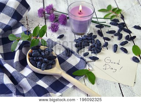 Spoon with honeyberry, note with good day text and candle. Beautiful summer vintage background, vegetarian and vegan concept, rural still life with berry and flowers