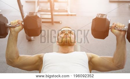 Bodybuilder Does Bench Press Using Dumbbells At The Gym. Muscular Man Exercising In The Gym