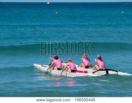 Mount Maunganui, New Zealand - January 28, 2012;  Four women in pink tops paddle surf outrigger canoe through surf in competitions at Mount Maunganui Surf Lifesaving 2012.