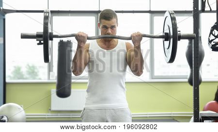 Athlete Doing Exercise For Biceps With Barbell. Young Muscular Man Trains At The Gym.