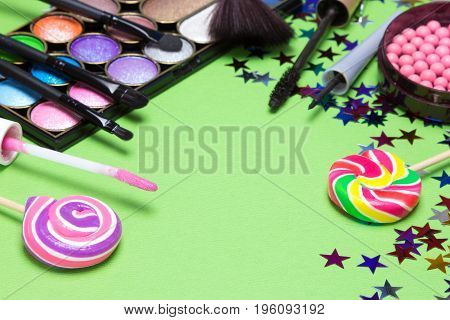 Make-up for festive party. Lip gloss, color glitter eyeshadow, blush, eyeliner, mascara, brushes with lollipops and confetti on green textured background. Copy space