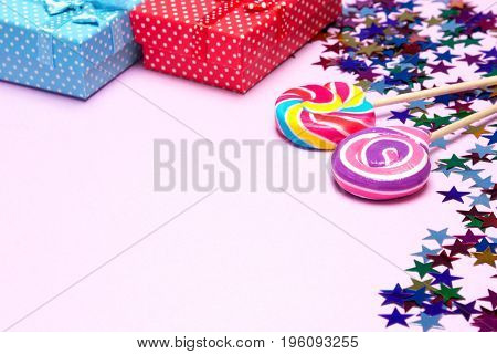 Holiday background. Lollipops, gift boxes and confetti on textured pink surface. Copy space