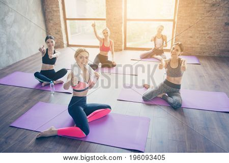 You Can Do It! Five Hot Ladies In Trendy Sports Outfit Are Showing Thumbups In A Gym, Sitting On A P
