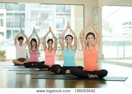 Group of asian people training yoga indoor class in namaste posture with joyful relax and meditate emotion wellness well being and healthy lifestyle concept