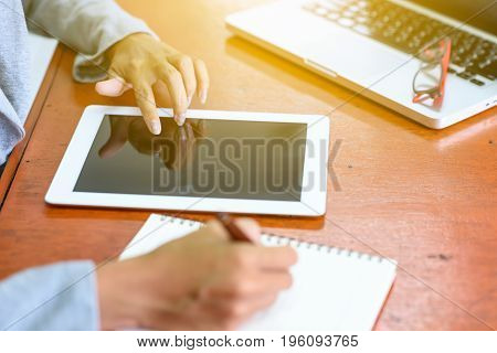 Beautiful Asian businesswoman is using and touching a tablet. At the same time he wrote the report with a pen on the table to her office. Finance Banking and Technology Concepts.