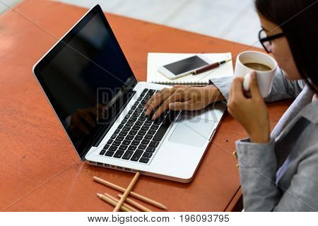 Businesswoman drinking coffee while working on a laptop computer.