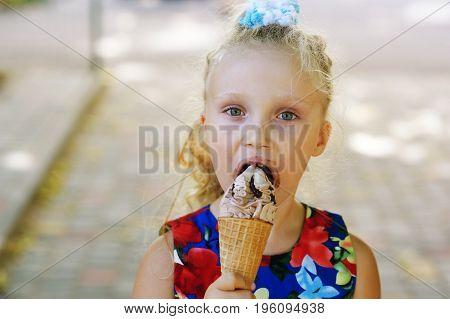 Little girl eating ice cream sloppy to get it .
