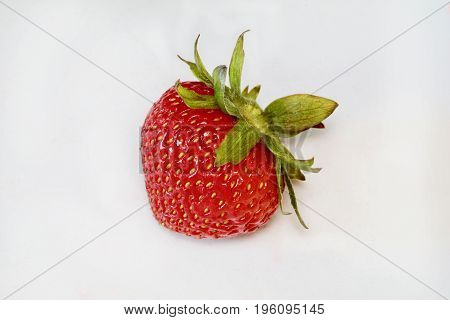 An imperfect strawberry is isolated on the white background.