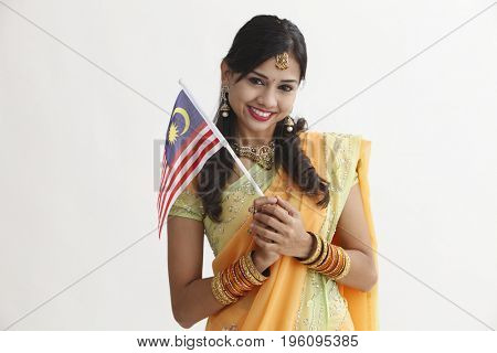 Indian woman in glamorous traditional clothing holding malaysia flag celebration merdeka
