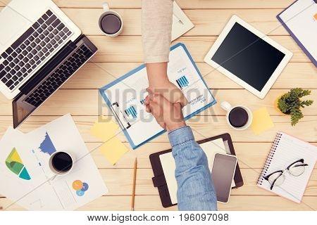 Confident business handshake. Top view of two business people shaking hands at office desk