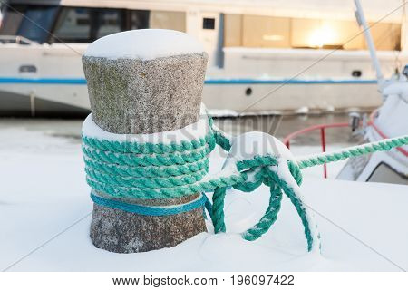 Snow covered bollard with mooring ropes at winter