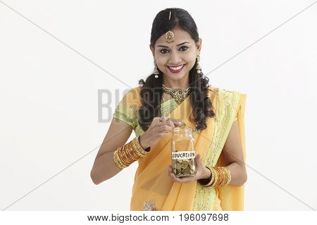 Indian woman in glamorous traditional clothing holding a saving jar