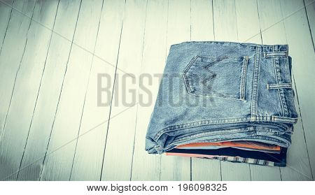 pile of jeans put on a wooden background with space vintage tone style.