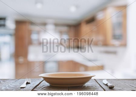 empty plate with fork and knife on wooden table in the kitchen