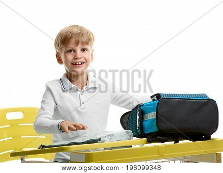 Happy young boy sitting at the desk and packing schoolbag