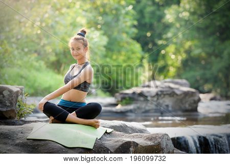 Beautiful Asian girl exercises and meditates with yoga on the rocks near the waterfall in the rain forest on the mountain. Health and Nature Concept.