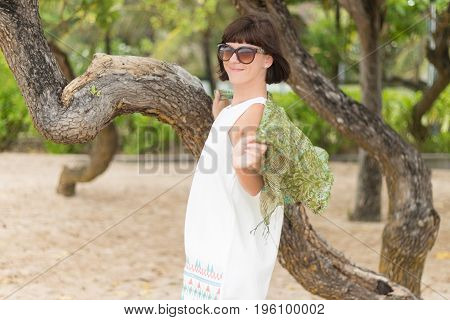 Beauty portrait of sexy brunette woman on the beach with colorful silk scarf and sunglasses. Cruise summer fashion.