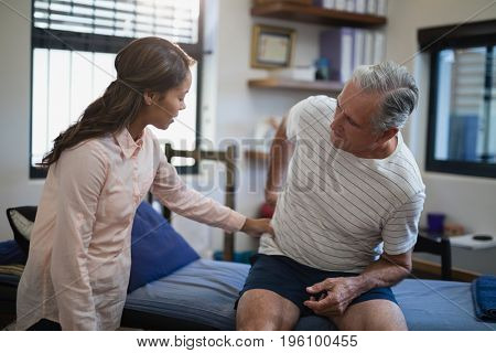 Female therapist examining back of male patient sitting on bed at hospital ward