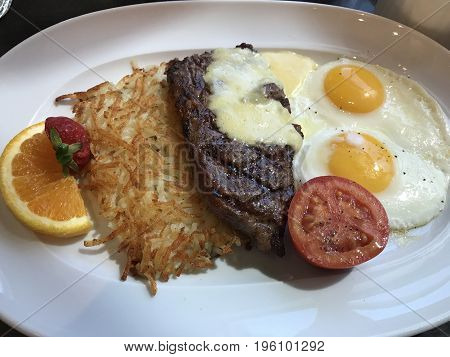 Steak and eggs with hashbrown. A hearty breakfast.