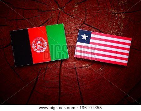 Afghani Flag With Liberian Flag On A Tree Stump Isolated