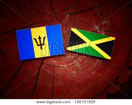 Barbados Flag With Jamaican Flag On A Tree Stump Isolated