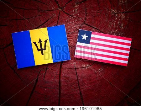 Barbados Flag With Liberian Flag On A Tree Stump Isolated