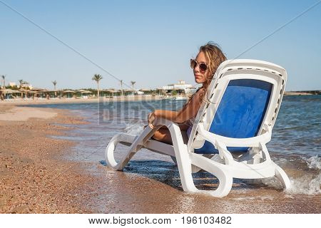 Pensive Young Woman In Sunglasses Is Sitting In A Deckchair, Against The Background Of The Sea And T